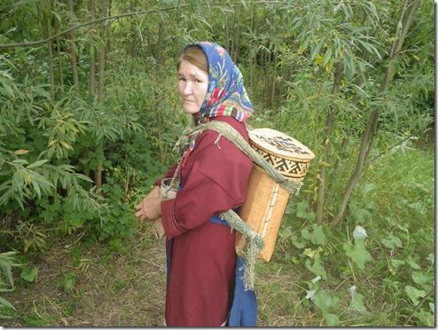 אישה מהשבט עם סל לליקוט אוכמניות